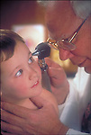 Doctor examining ear of young boy with an otoscope