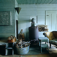 In the living room wood is stored next to an antique stove in preparation for a harsh winter
