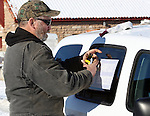 Kenneth Medenbach, of Crescent, Ore was arrested under suspicion of operating an unauthorized vehicle when he left the refuge for trip to the local Safeway to puchase groceries. Here, he is pictured replacing door signage on a government vehicle from the Malheur National Wildlife Reserve on January 15, 2016 in Burns, Oregon.  A second government vehicle, which like the first was reported stolen by the U.S. Fish & Wildlife Service, was found next to Medenbach's in the Safeway parking lot .  © 2016. Jim Bryant Photo. All Rights Reserve.