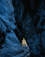 A triangle of light appears through the bluish shaded walls of Refrigerator Canyon