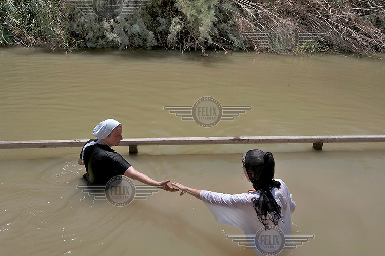 Christian pilgrims wade in the Jordan River, at the baptism site of Qasr el-Yahud, near Jericho. The site is traditionally believed to be the place where Jesus was baptised.