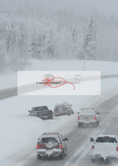 While the weekend's snowstorm continued, a pair of vehicles lie abandoned in the Eagle River hill median Saturday afternoon.  Photo for the Star by  Michael Dinneen