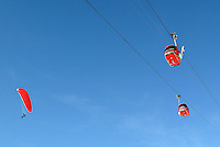 Switzerland. Valais. Crans Montana. Winter ski resort. CMA ( Crans Montana Aminona) red cable cars are carrying people to the top of the mountain, while man with a red parachute goes down to the valley. Blue sky on a nice weather day.  © 2005 Didier Ruef