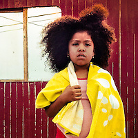 A young girl with afro hairstyle (originally from Chincha province) stands in front of a wooden house in Pachacútec, in the northern outskirts of Lima, Peru, 20 January, 2015.