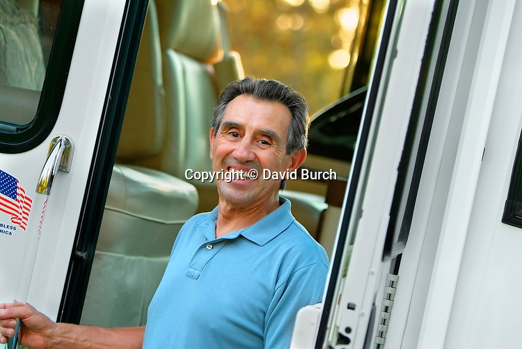 Hispanic man standing next to his rv