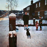 Tommy, wearing shorts, with two of his granddaughters and a dog in his front yard in the snow in Upper Ardoyne, Belfast.