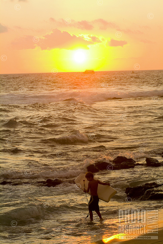 A young boy holding a body board enters the ocean with a beautiful glowing sunset reflected in the waves at Hano beach in Kona on the Big Island of Hawaii.