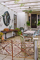 Antique iron sink used as planter outdoors on the patio next to house, with Begonia in container garden, Bromeliad houseplants, other antiques hanging on wall as rustic ornaments in a garden room with overhanging arbor trellis with vines