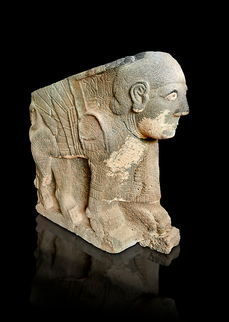 Pictures & images of the North Gate Hittite sculpture statue depicting a mythical winged god with a human head. 8the century BC.  Karatepe Aslantas Open-Air Museum (Karatepe-Aslantaş Açık Hava Müzesi), Osmaniye Province, Turkey. Against black background