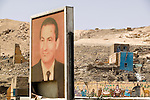 An image of Egypt's president Muhammad Hosni Said Mubarak stands across the road from the part of Qurna where houses have been demolished the most. This is also the area previously known as an alabaster centre, where tourists would stop and buy handcraft directly from shops managed by villagers..Qurna, Luxor, Egypt..Photo: Eduardo Martino