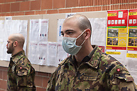 "Switzerland. Canton Ticino. Rivera. Monte Ceneri military base. Due to the spread of the coronavirus (also called Covid-19), the Federal Council has categorised the situation in the country as ""extraordinary"". The army was called upon to provide logistical support and to offer its skills in terms of medical assistance (ambulances, field hospital, tents, nurses,..). The militia soldiers from medical troops were called by the Swiss army for the first time since World War II. Under the country's militia system, professional soldiers constitute a small part of the military and the rest are conscripts or volunteers aged 19 to 34 (in some cases up to 50). Two soldiers wait to wash their hands before entering the refectory. A bald man wears a mask in front of his mouth. On the wall, the Coronavirus poster explains how to prevent from getting the disease. The measures are: Keep your distance, wash your hands thoroughly, avoid shaking hands, cough and sneeze into a tissue or the crook of your arm, stay at home if you have fever, always call ahead before going to the doctor's or the emergency department. Monte Ceneri is a mountain pass in the canton of Ticino. It connects the Magadino plain and the Vedeggio valley across the Prealps. 2.04.2020 © 2020 Didier Ruef"