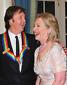 Sir Paul McCartney, one of the 2010 Kennedy Center honorees, shares some thoughts with United States Secretary of State Hillary Rodham Clinton as they prepare to pose for their formal class photo following the formal Artist's Dinner at the United States Department of State in Washington, D.C. on Saturday, December 4, 2010..Credit: Ron Sachs / CNP.