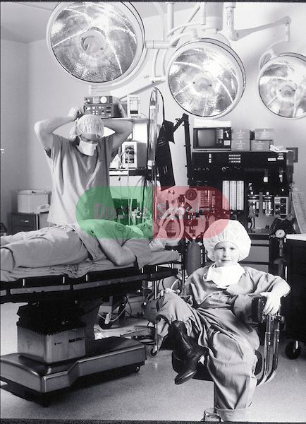 young boy dressed as surgeon sitting in chair, adults goofing around in hospital operating room