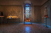 Cabinets of censers and of monstrances, with blue and gold glass beads made with Murano glassmaker Salviati, in the Bell tower room themed 'Le Merveilleux' or The Supernatural, first floor, in Le Tresor de la Cathedral d'Angouleme, in Angouleme Cathedral, or the Cathedrale Saint-Pierre d'Angouleme, Angouleme, Charente, France. The 12th century Romanesque cathedral was largely reworked by Paul Abadie in 1852-75. In 2008, Jean-Michel Othoniel was commissioned by DRAC Aquitaine - Limousin - Poitou-Charentes to display the Treasure of the Cathedral in some of its rooms, which opened to the public on 30th September 2016. The cement floor tiles made by MiraColour and the hand printed wallpaper by Atelier d'Offard, both use interlacing patterns reminiscent of the Neo-Romanesque period of the 19th century. Picture by Manuel Cohen. L'autorisation de reproduire cette oeuvre doit etre demandee aupres de l'ADAGP/Permission to reproduce this work of art must be obtained from DACS.