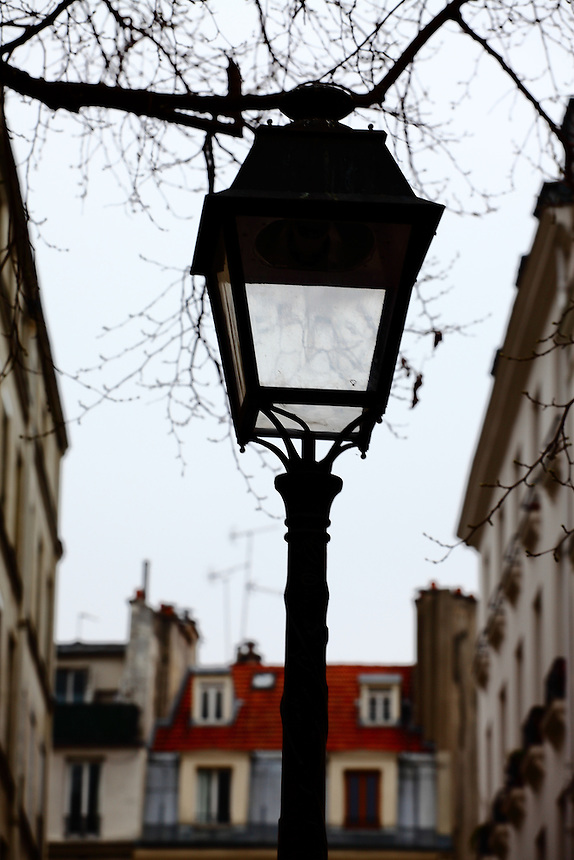 The top of a street lamp in a quiet small square of the Marais, in Paris, onto the background of the typical old buildings surrounding it. It was a cloudy day. Digitally Improved Photo.