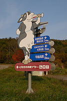 "A signpost in Kuzumaki advertising local dairy and wine products. Kuzumaki in Northern Japan bills itself as a town of ""Milk, wine and clean energy"". The 8000 population town has little local industry so Kuzumaki invited Japanese companies to set up wind, solar and biogas generating plants."