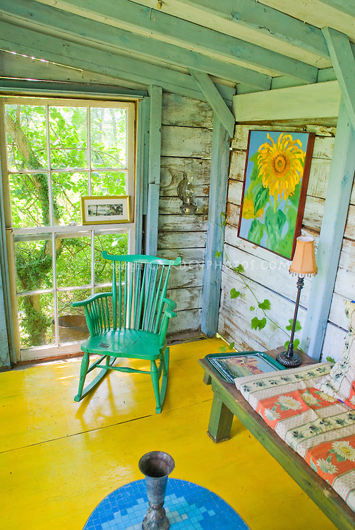 Porch of house with painted wood floor, bright colors, rustic eclectic furniture rocker, vintage shabby chic style