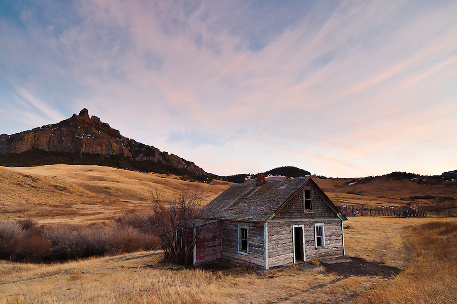 An abandoned homestead in Cascade County, Montana is seen near sunset with a mountain in the background.