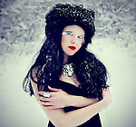 A pale girl with black hair and red lipstick wearing a black fur hat and standing in a forest in the snow.