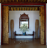 View through open sliding bamboo doors to an antique Peruvian mirror in the entrance to the beach house