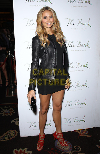 Stacy Keibler.Stacy Keibler Hosts Big Game Eve at The Bank Nightclub inside The Bellagio, Las Vegas, Nevada, USA, .4th February 2012..full length back dress leather jacket red strappy shoes sandals mini clutch bag .CAP/ADM/MJT.© MJT/AdMedia/Capital Pictures.