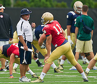 Strength coach Paul Longo talks with quarterback Tommy Rees (11).