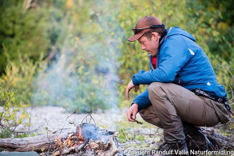Mann koker kaffe på bålet. ---- Man making coffe on open fire.