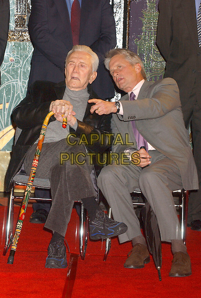 KIRK DOUGLAS & MICHAEL DOUGLAS.During the Jack Valenti Immortalized with Hand and Footprint Ceremony held at Grauman's Chinese Theatre, Hollywood, California, USA, .December 06 2004.full length sitting father son dad family walking stick cane pointing.Ref: ADM.www.capitalpictures.com.sales@capitalpictures.com.©Laura Farr/AdMedia/Capital Pictures .