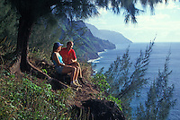 Couple enjoys the view at the beginning of the trail to Kalalau Valley, Na Pali Coast, north shore, Kauai