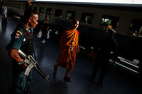 A Buddhist monk passes by an armed man securing the train station in the troubled Pattani province in southern Thailand February 28, 2011. Separatists are blamed for most of the attacks on Thailand's predominantly Muslim deep south, which often target Buddhists and Muslims associated with the Thai state, such as police, soldiers, government officials and teachers. No credible group has claimed responsibility for near daily drive-by shootings and bombings, which continue unabated, despite a massive counterinsurgency effort. Yala and Pattani are two of three Muslim-dominated provinces bordering Malaysia where more than 4,300 people, both Muslims and Buddhists, have been killed in a low-level insurgency since 2004.   REUTERS/Damir Sagolj (THAILAND)