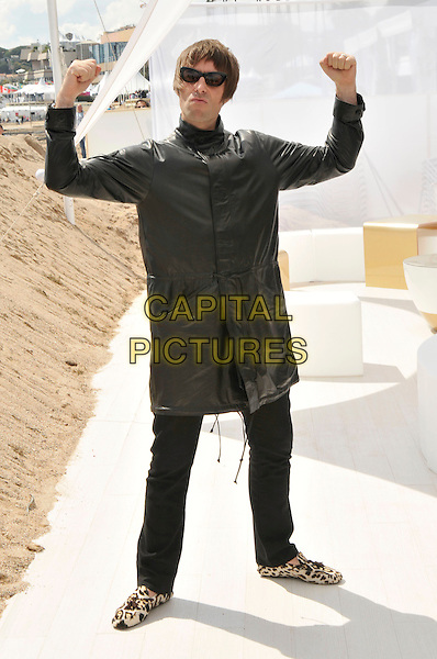 "LIAM GALLAGHER.his newest production company 'In 1 Productions' announces thay will produce a Beatles film based on the book by Richard DiLello:.""The Longest Cocktail Party' photocall.63rd International Cannes Film Festival, France.14th May 2010.full length black leather jacket jeans denim sunglasses shades arm in air leopard print loafers shoes fists flexing muscles.CAP/PL.©Phil Loftus/Capital Pictures."