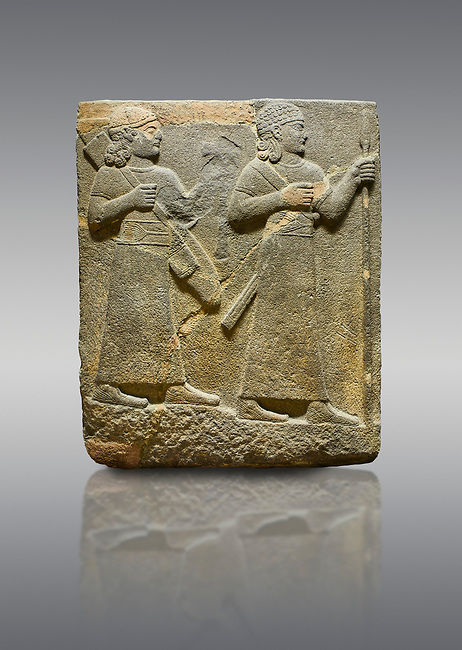 Picture & image of Hittite relief sculpted orthostat stone panel of Royal Buttress. Basalt, Karkamıs, (Kargamıs), Carchemish (Karkemish), 900-700 B C. Warriors. Anatolian Civilisations Museum, Ankara, Turkey.<br /> <br /> Two figures are seen, each with a long dress, a thick belt and curled hair. The figure in front carries a spear in his left hand and a long sword at his waist, and the figure behind carries an axe in his left hand and a quiver on his back.   <br /> <br /> Against a gray background.