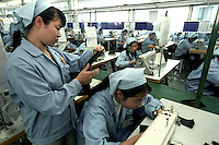 Factory workers operate sewing machines at a factory in Guangzhou..17-JAN-03