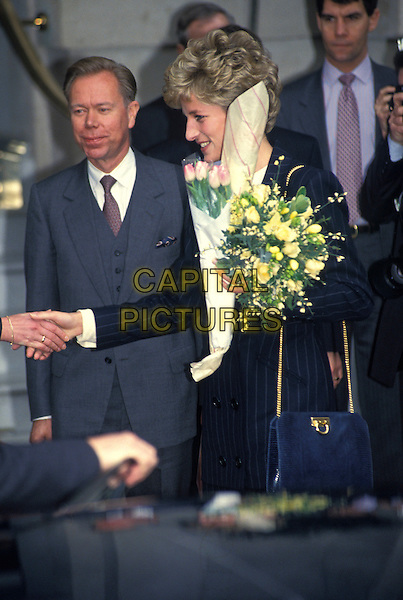 HRH PRINCESS DIANA, THE PRINCESS OF WALES.Langham Hilton Hotel, London , England,.16th February 1993..royal Lady Di half length navy blue pinstripe suit jacket skirt flowers shaking hands profile.CAP/HT.©Hugh Thompson/Capital Pictures