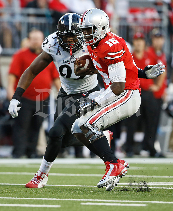 Ohio State Buckeyes quarterback J.T. Barrett (16) rushes past Cincinnati Bearcats defensive lineman Silverberry Mouhon (92) during the second quarter of the NCAA football game at Ohio Stadium in Columbus on Sept. 27, 2014. (Adam Cairns / The Columbus Dispatch)