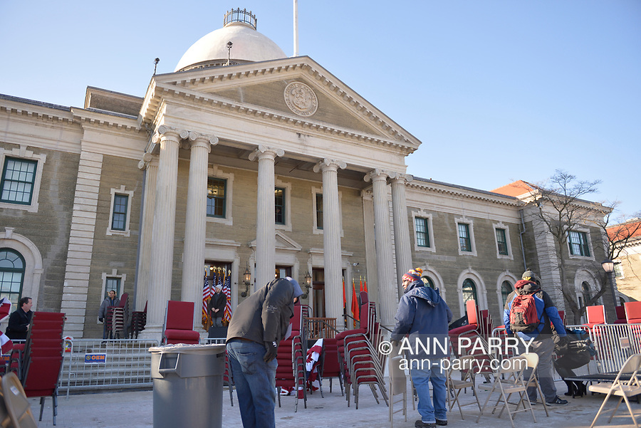 Mineola, New York, USA. January 1, 2018. Workers remove chairs, flags, bunting from location the swearing-in ceremony of Laura Curran as Nassau County Executive was just held, in front of Theodore Roosevelt Executive & Legislative Building. Temperature was a freezing 14 ℉ Fahrenheit / -10 ℃  Celsius for the outdoor event.