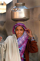 Woman carrying a container of water on her head in the village of Bagar, Rajasthan, India.