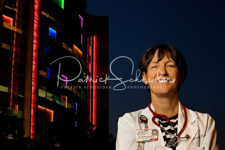 Levine Children's Hospital Dr. Susan Massengill in front of the colorful nighttime view of the hospital at Carolinas Medical Center in Charlotte, North Carolina.