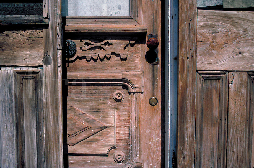 Three weathered wooden doors stand next to each other in New Orleans' French Quarter. New Orleans Louisiana USA.