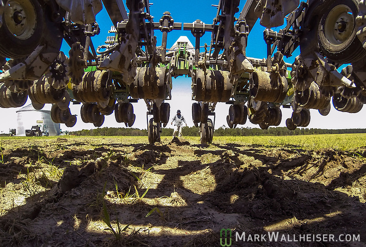 Worker Renato Lamas check the planter after hitting a rock in the field near Valdosta, Ga. April 1, 2014.