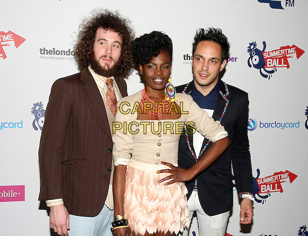 THE NOISETTES - Jamie Morrison, Shingai Shoniwa & Dan Smith.The Capital FM Summertime Ball at the Emirates Stadium, London, England. June 7th, 2009.half length black jacket brown dress skirt cardigan hand on hip pink white beard facial hair necklace one earring .CAP/MAR.© Martin Harris/Capital Pictures.