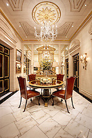 An opulent dining room with a mirrored wall and gilded ceiling. The room is furnished with a round pedestal table and brown leather dining chairs.