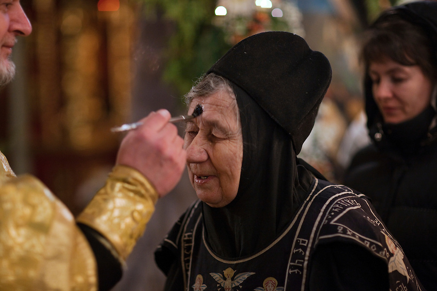 Moscow, Russia, 06/01/2011..A priest makes uses holy water to make the sign of the cross on a nun's forehead as Russian Christians attend an Orthodox Christmas service at Peter Paul church in central Moscow, late on Christmas Eve. Christmas falls on January 7 for Orthodox believers in the Holy Land, Russia and other Orthodox churches that use the old Julian calendar instead of the16th-century Gregorian calendar.