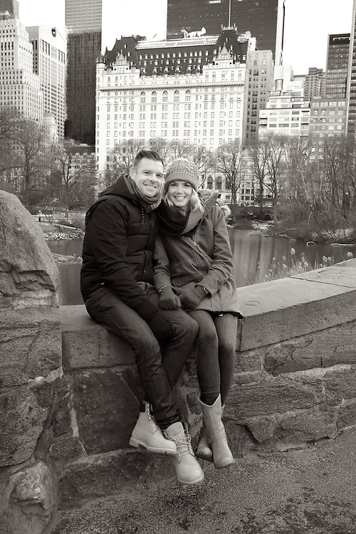A just engaged couple sitting on a bridge in Central Park with The Plaza Hotel in the background.