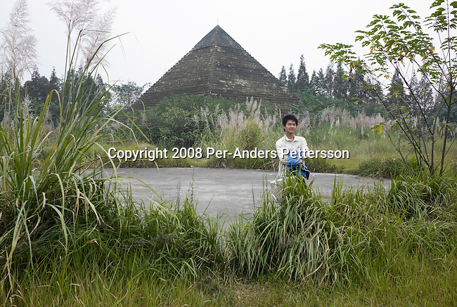 CHENGDU, CHINA OCTOBER 9: A student stands in front of a copy of an Egyptian pyramid at Chengdu World Paradise Theme Park on October 9, 2008 in Chengdu, China. The park closed in 2004 due to lack of funds and visitors. Some of the attractions are still there such as a Statue Of Liberty and Rialto bridge from Venice, Italy. Now its serves as a College and many students and teachers live there. Chinese people love theme parks and new ones are opening constantly. It's estimated that there's about 2400 theme parks in the country. Because of the tougher competition, some parks close down. (Photo by Per-Anders Pettersson) ..