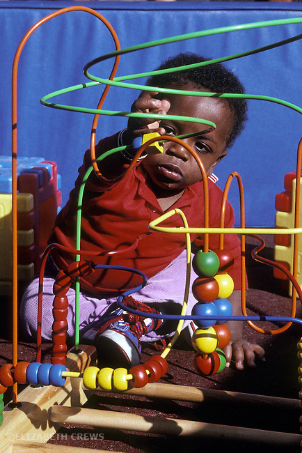 Berkeley CA Boy, seventeen-months-old exploring bead toy at day care