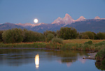 Idaho, Eastern, Teton Valley, Driggs. Full moon rise over the Teton Range and the Teton River in early autumn.