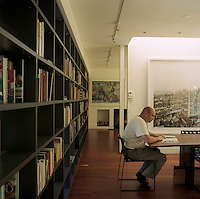 The owner of the property reads in the open-plan library-cum-dining room which is separated from the living room by a partition wall