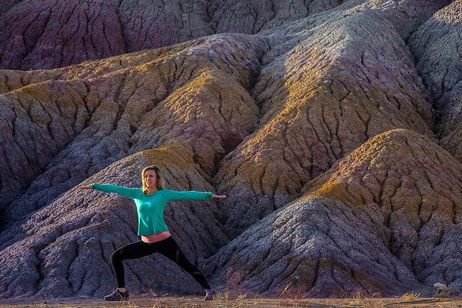Model practices yoga moves in front of colorful clay beds in Southern Utah