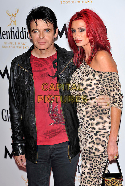 GARY NUMAN & guest.Glenfiddich Mojo Honours List Awards 2011 at The Brewery, London - 21st July 2011.half length brown beige leopard print dress off the shoulder dress black leather jacket red top .CAP/ROS.©Steve Ross/Capital Pictures